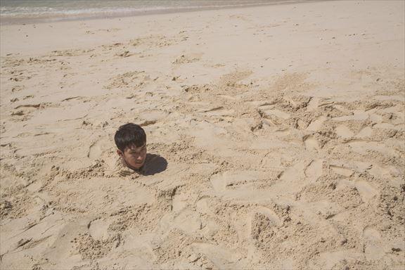 砂浜に埋まり自身の影で方角を確認する男性 [モデル:大川竜弥]