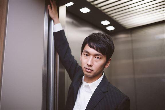 「私、何階に行くと思います?」と難解なクイズを出す若き経営者 [モデル:大川竜弥]_R