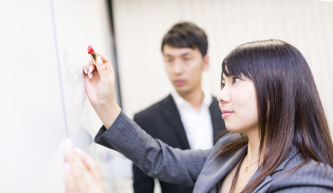口紅でホワイトボードにメッセージを書く女性社員 [モデル:大川竜弥 Lala]_R