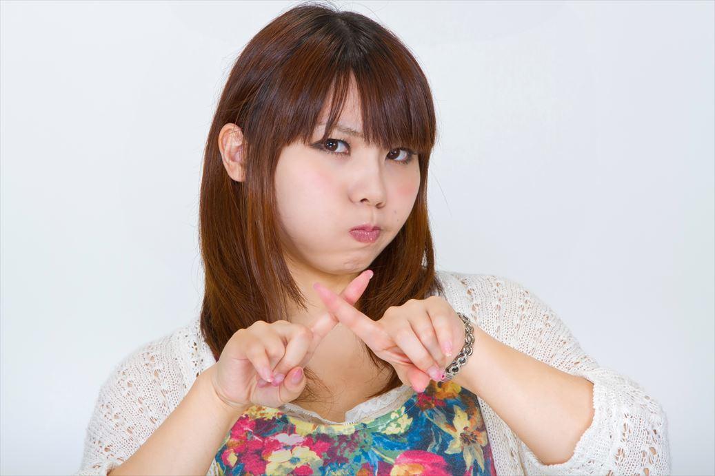 頬を膨らませてバツをする女性 [モデル:Lala]_R