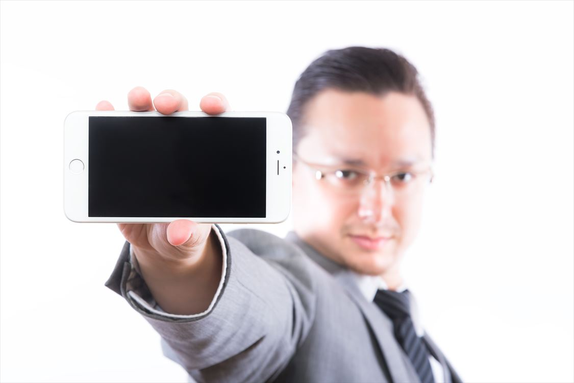 iPhone6の画面を見せるエンジニア [モデル:Max_Ezaki]_R