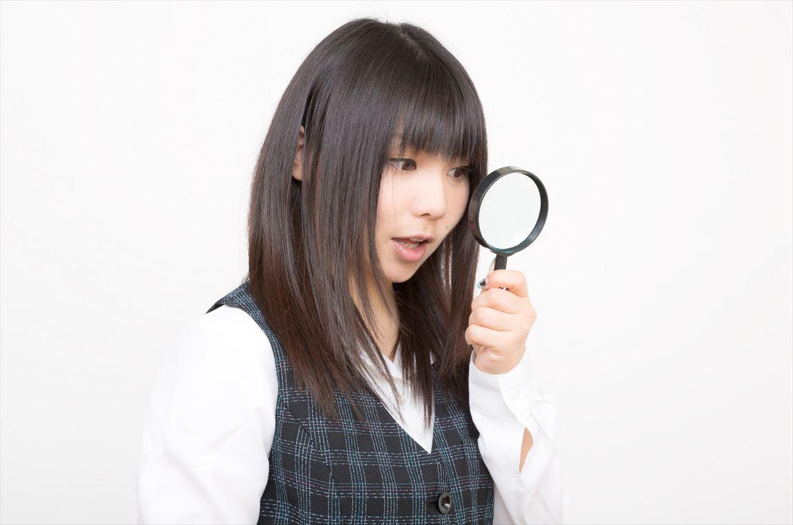 虫眼鏡を覗きこむOL [モデル:Lala]