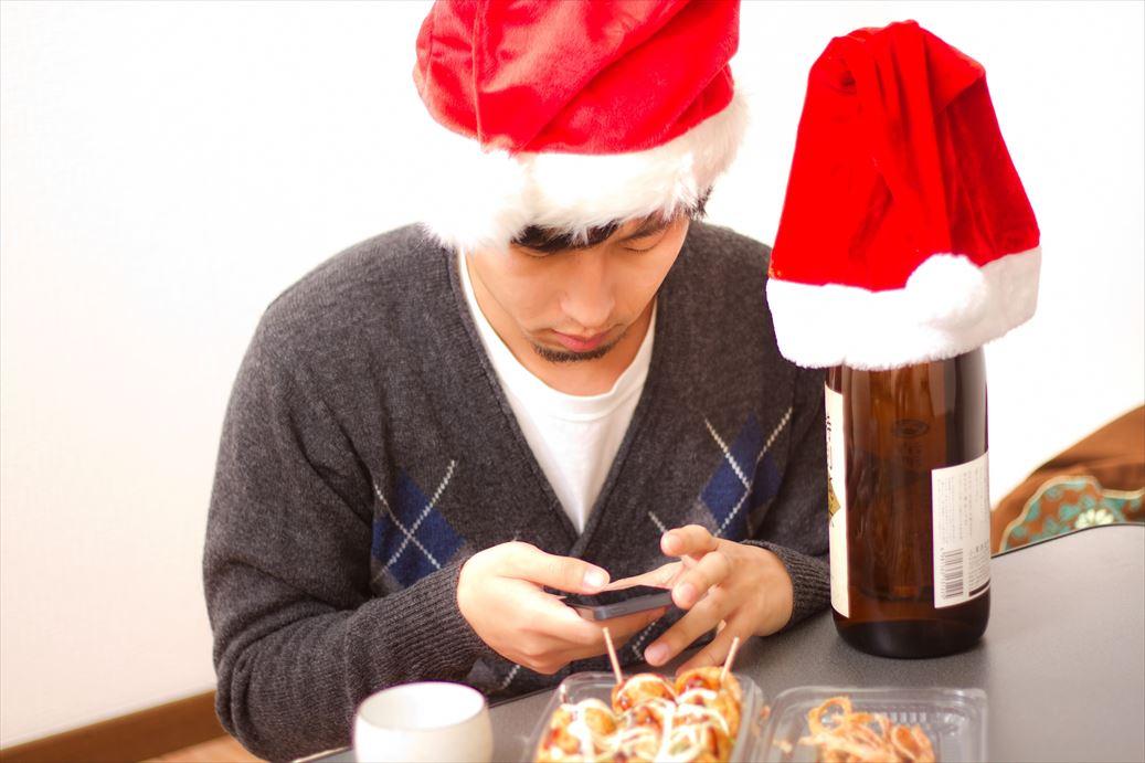 メールが来ているかiPhoneを確認するサンタ帽をかぶったクリぼっち [モデル:大川竜弥]_R