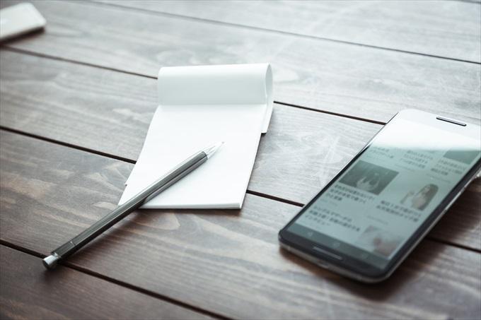 スマートフォンとメモ帳とペン